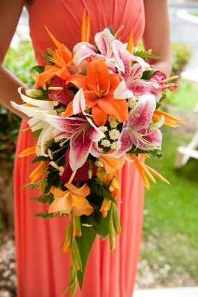 orange tiger lilies, pink stargazer lilies, orange gladiolus, white pompons, red anthuriums, leatherferns,  bird of paradise cascade.