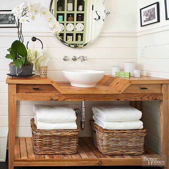 Often tucked away and short on square footage, the powder room is an understated space that's relatively easy to revamp. This reclaimed pine desk boasts a modest bowl sink and wall-mount faucet for plenty of counter space. Open shelving underneath creates an ideal spot for baskets to hold extra towels and toiletries.