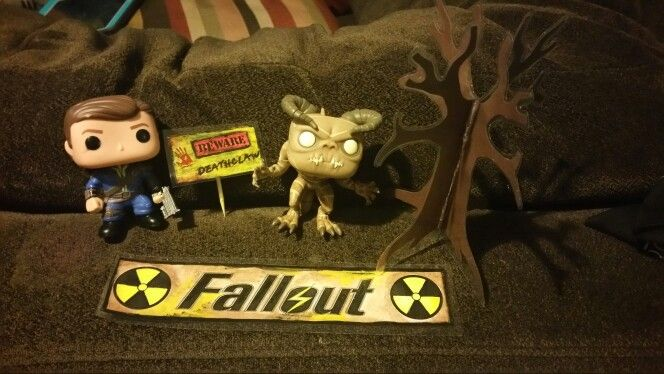 """Fallout Birthday Cake Toppers Funko Pop Fallout figures with a handmade, painted and laminated """"death claw"""" sign, laminated """"fallout"""" logo, and laminated 3D paper tree for added effect. Can't wait to see it on the cake!"""