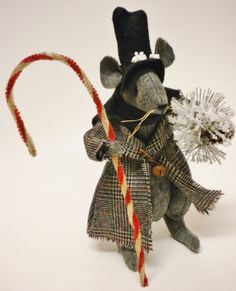 This handsome Victorian Christmas Mouse great for Winter Decorating! The Made To Order Mouse has black bead eyes, whiskers, and wired arms and legs for positioning. The Primitive Mouse wears a plaid coat, black top hat and scarf accented and pinned with rusty bell. In one had he has
