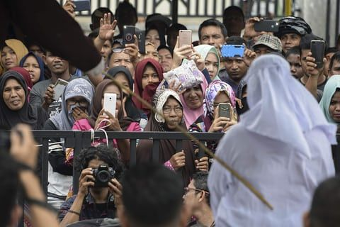 A crowd watches as an Indonesian Christian woman is publicly flogged for violating Islamic law in Banda Aceh, Indonesia