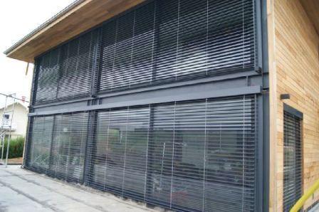 Grandes baies vitrées en alu noir sur maison en ossature métallique