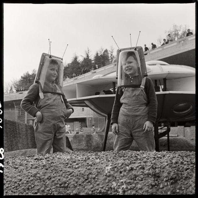 Vue sur le paysage lunaire et plus particulièrement sur les enfants jouant dans les cratères. Certains enfants portent des casques spéciaux de cosmonaute. A l'arrière-plan, on observe la station spatiale et le télécanapé. On aperçoit également le pavillon de la rotonde et la passerelle. © Musée historique de Lausanne #expo64 #Lausanne