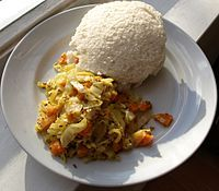 Ugali is pictured here with a side dish of cabbage, though it is more typically eaten with kale (Sukuma wiki).