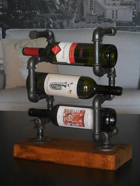 Industrial wine bottle display made of black fittings and pipes and wooden base. The wooden base is hand-crafted and processed with blow-torch and painted with