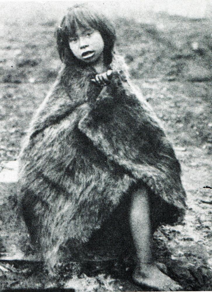 """Niña alacalufe con capa de piel. Fotografía de Martín Gusinde. 1920 aprox. En: """"Los indios de Tierra del Fuego: los Halakwulup"""""""". Martín Gusinde. Editorial C.A.E.A .1986."""