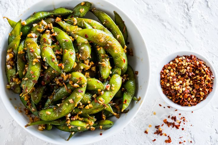 A simple and delicious recipe for spicy garlic edamame, a quick 10-minute appetizer loaded with fresh garlic, chili oil, and spicy red pepper flakes.