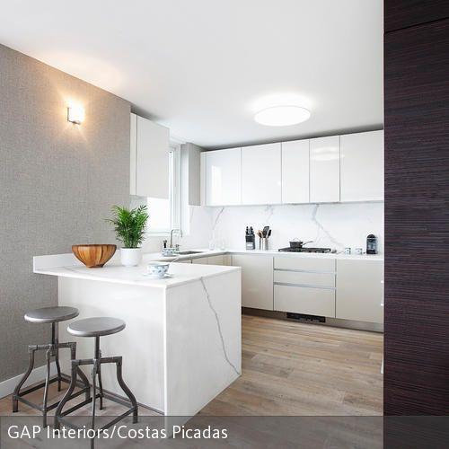 Die Hocker im Industrie-Chic verleihen der offenen Küche in Weiß einen coolen Touch. Natürliche Accessoires wie Holzschale und Zimmerpflanze setzen zudem…