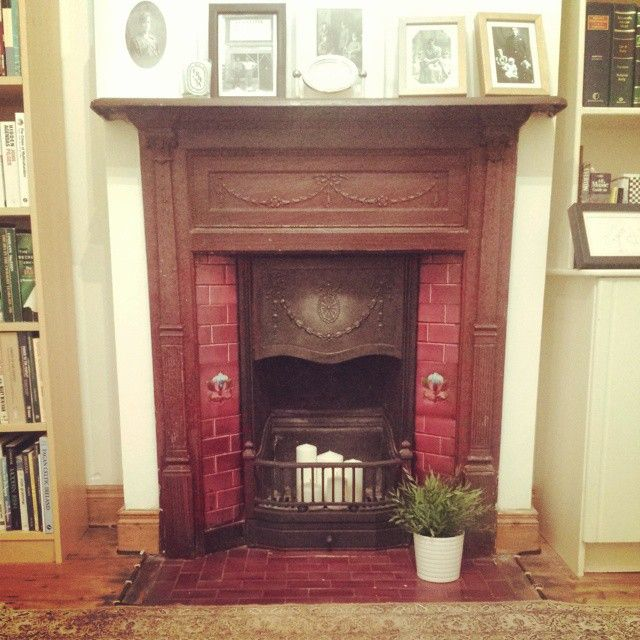 The original fire surround from my house probably dates from early 1900s. Old family photos on the mantel. Vintage clock from a carboot sale. Plant from Ikea. Candles in the grate are from Next Home.  #livingroom #house #home #mantelpiece #firesurround #ireland #interior #design #decor #oldphotos #family #candles