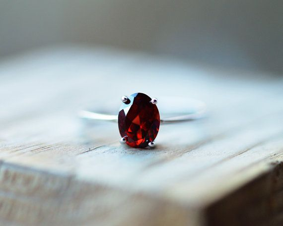 This dainty ring features a very rich, deep brownish red, 1.5 carat oval cut natural garnet, set in .925 solid sterling silver. Very comfortable to wear and absolutely stunning in natural light.  Jewellery Specifications:  Metal: .925 marked solid sterling silver Finish: Rhodium plated Gemstone: 1.5ct natural African garnet Stone dimensions: 7 x 5mm Colour: Rich red, highlights brownish red, excellent quality  ~*I am not a professional photographer, and although colours will vary from…