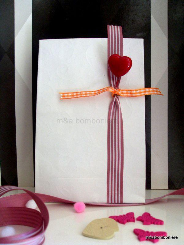 Μια πιο ιδιαίτερη μπομπονιέρα, για εσάς που επιμένετε να αγαπάτε το λευκό... και έχετε τόσο δίκιο... Σε λευκό σακουλάκι με ανάγλυφη επιφάνεια, διακοσμημένη με μια κατακόκκινη καρδιά και όμορφες κορδέλες. Τιμή: 2,00 ευρώ.