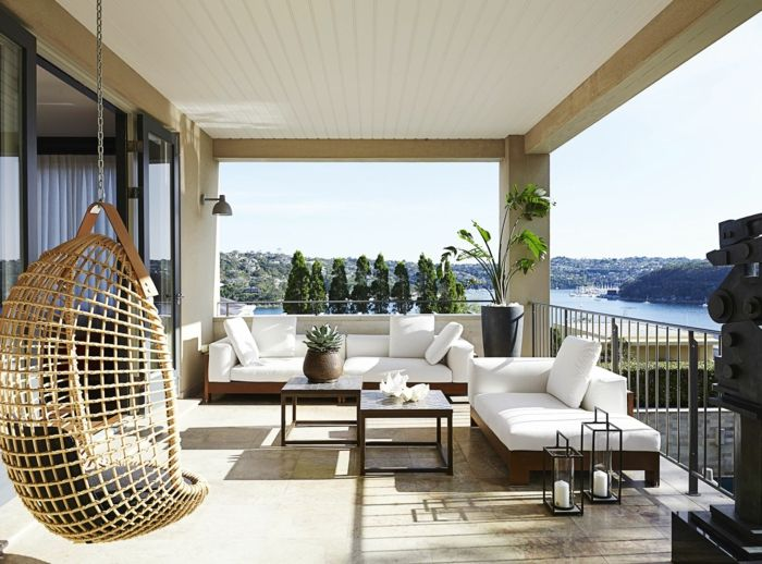 ideas-decoracion-terrazas-sillon-colgante-moderno-de-mimbre-muebles-de-madera-tapizadas-en-blanco-decoracion-de-plantas-verdes-y-bonita-vista-al-mar