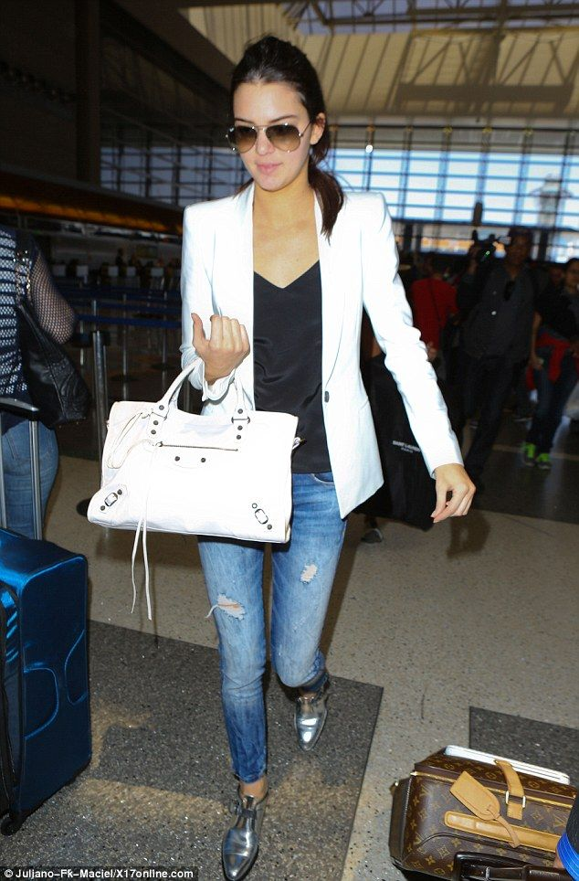 Travel chic: Kendall Jenner wore a white blazer, silky tank top, skinny jeans and silver shoes
