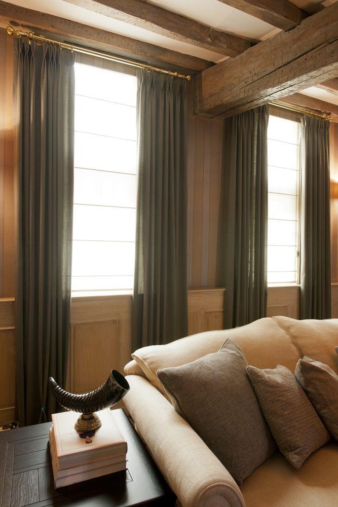 Kamerhoge gordijnen accentueren het hoge plafond en maken de ruimte warm en intiem. De goudkleurige gordijnroede vloeit over in het cognacbruin van de wand en de houten balken. Of hoe een roede, gordijn en interieur perfect met elkaar kunnen versmelten.