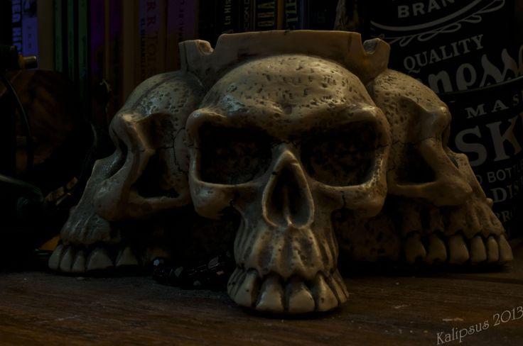 """""""Cosas por qué morir"""" Al frente el cenicero de cráneos con dos tipos de luz, de fondo tres cosas por las que moriría...libros, películas y whisky."""