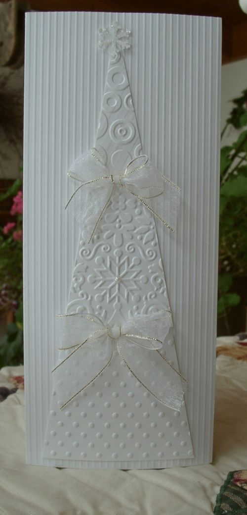 handmade Christmas card ... tall and thin format ... white on white ... triangular tree with three sections of different embossing folders ... punched and glittered tree topper .. organdy bows cover the lines between layers ... background hand embossed with narrow lines ... awesome card!!