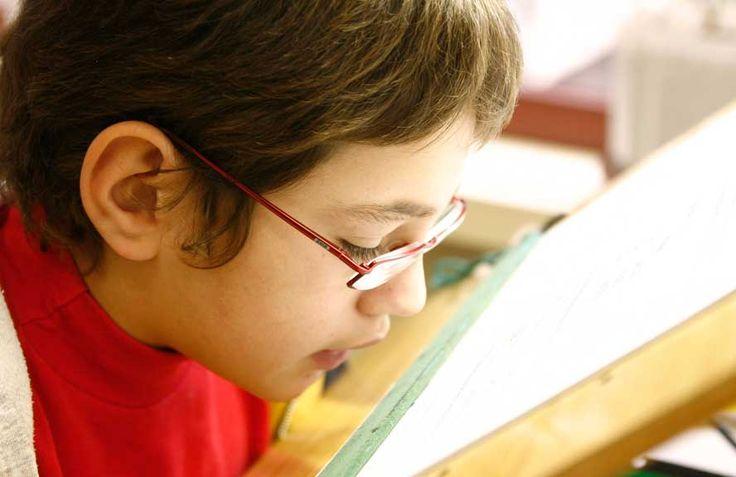 Alumno con deficiencia visual utilizando su resto visual para leer