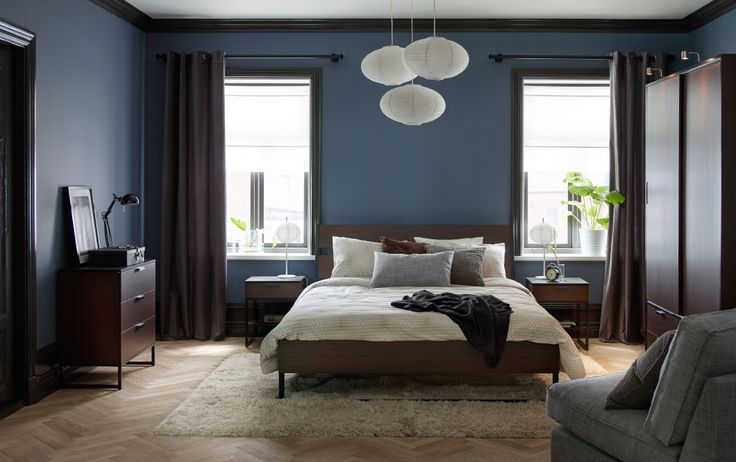 A large bedroom with a dark brown bed for two with bedlinen in beige and grey. Combined with bedside tables, chest of drawers and a wardrobe, all in dark brown.