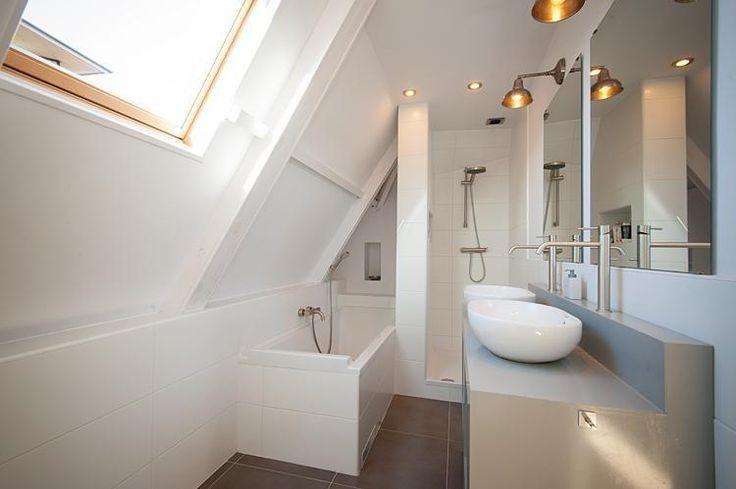 Cette salle de bain sous les combles utilise la sous pente pour la baignoire. Malin !