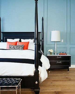 Blue paneled walls, glossy black poster bed, orange and zebra accent pillows, tufted black patent leather bench - LOVE this look!