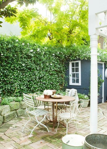 Intertwined jasmine and potato vines overflow this courtyard, above a French cafe-style outdoor setting - Home Beautiful
