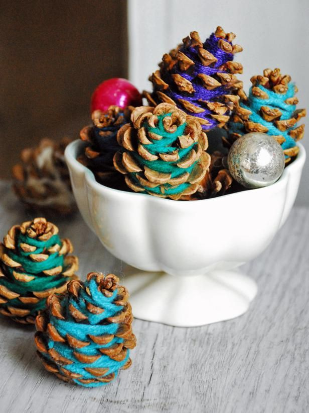 42080577741865676 Yarn Pinecones  Add a different spin to your holiday decor with these simple, colorful pinecones. All you need to do to create this look is wrap bright strands of yarn around pinecones — no glue required. They make perfect embellishments for gifts or placed in a bowl as a centerpiece.