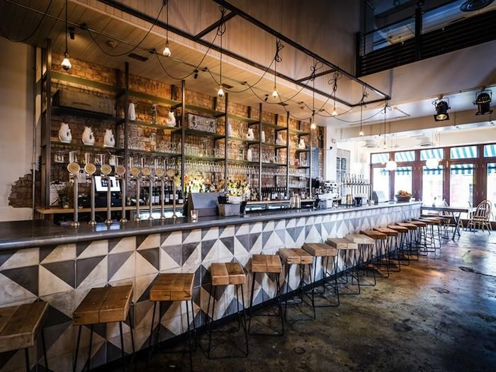 Beautiful The Long Bar Counter Is Clad In Black And White Geometric Pattered Tiles,  Paired With Bar Stools Made From Tubular Black Steel And Wooden Planks.