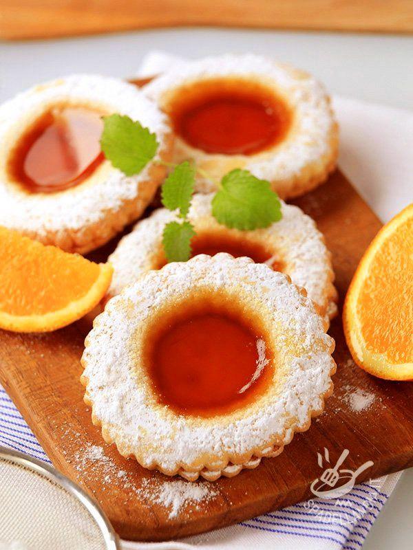 Gli Occhi di bue all'arancia, a base di una squisita pasta frolla e un ripieno di marmellata profumata, sono intramontabili. Ideali per tutta la famiglia!