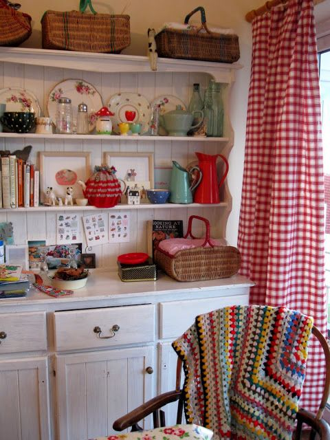 White painted hutch with variety of items on shelves. Red and white, colorful.