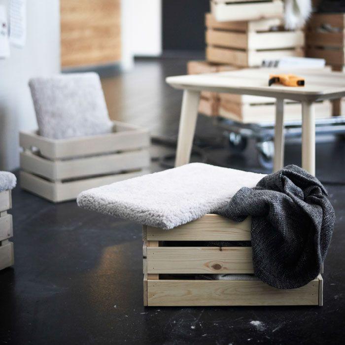 IKEA KNAGGLIG Kästen. Darauf Deckel mit grauem Schaffell überzogen.