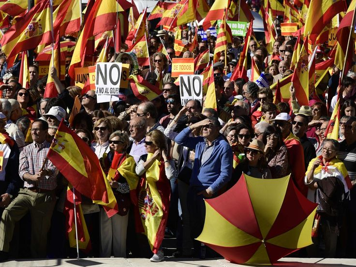 """People hold signs reading """"No to the coup"""" while waving Spanish flags during a demonstration calling for unity at Plaza de Colon in Madrid on Oct. 28, 2017, a day after direct control was imposed on Catalonia over a bid to break away from Spain.  Javier Soriano, AFP/Getty Images"""