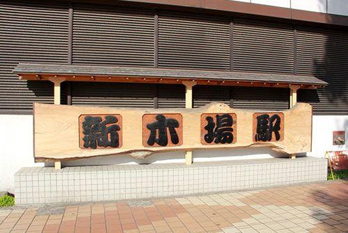 木材で出来た駅名表示板
