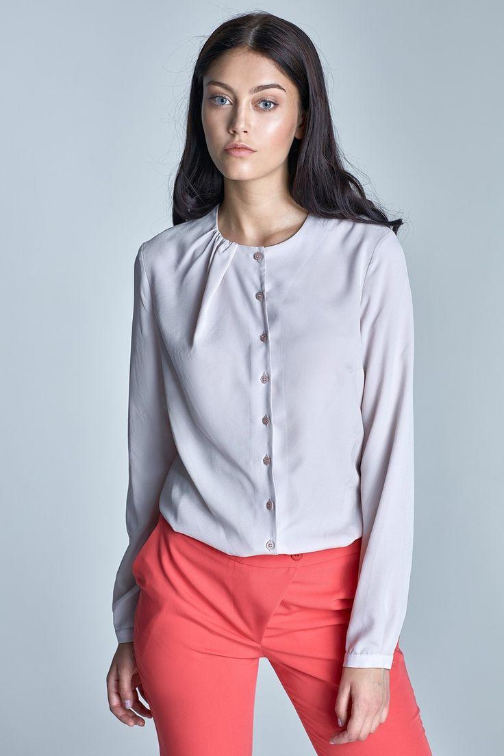 Niepowtarzalna bluzka koszulowa z długimi rękawami zakończonymi wąskimi mankietami. Urzeka swoją prostotą i delikatnym wyglądem. Okrągły dekolt zdobią ciekawe marszczenia. Zapinana z przodu na guziki. Wykonana z miękkiego, miłego w dotyku materiału. Dostępna w sześciu modnych wariantach kolorystycznych. Świetnie sprawdzi się na co dzień w pracy oraz w kreacjach na wyjścia okolicznościowe.