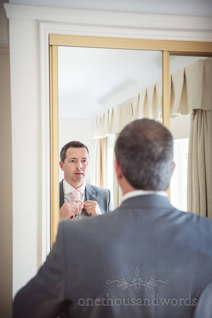 groom in grey wedding tail suit adjusts pink cravat in mirror on wedding morning. Photography by one thousand words wedding photographers