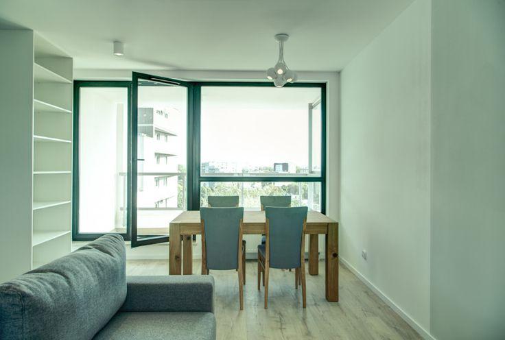 Kącik jadalniany umieszczony w centralnej części salonu, posiadający dostęp do naturalnego światła dziennego. Drewniany stół z tapicerowanym kompletem krzeseł wyróżnia się na tle minimalistycznego, szarego wnętrza.