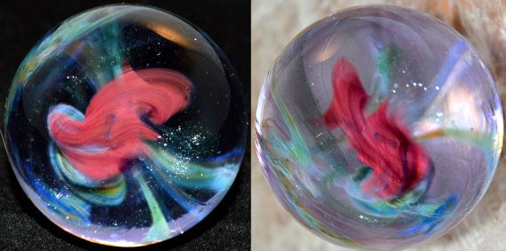 This marble features an encased Black Gilson Opal Cube suspended inside a galaxy of Dragons Blood and Blue Moon filled with sparkly stars. The space around the galaxy is a blend of clear, translucent purple and Green Stardust. Pictures cannot do justice to the depth, complexity and