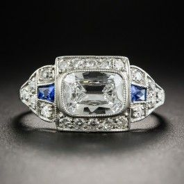 A gorgeous glistening icy white antique cushion-cut diamond, weighing 1.02 carats is presented horizontally in this chic and sophisticated Art Deco engagement ring, masterfully hand fabricated in platinum, circa 1920s-30s. The striking geometric architecture glitters with small single-cut diamonds accented by a pair of vibrant royal blue tapered scissor-cut sapphires.Currently ring size 6 1/2