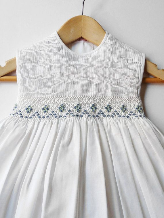 Charming smocking dress in White. Its made with a lightweigh fabric of cotton batiste 100% Great work in the chest, with a lot of raised embroidery with nine beautiful bouquets in blue. The light formal dress for summer days. With lined skirt with the same fabric, ended with scalloped stitches. In back tied with a ribbon and bowl in the same fabric. 32 = 81cm. X 1,5 = 3,5 cm.  Measurements: * length from shoulder are 19 1/4 in. = 49 cm. + a hem 1 3/4 = 4,5 cm. * waist lenght from shoulder…
