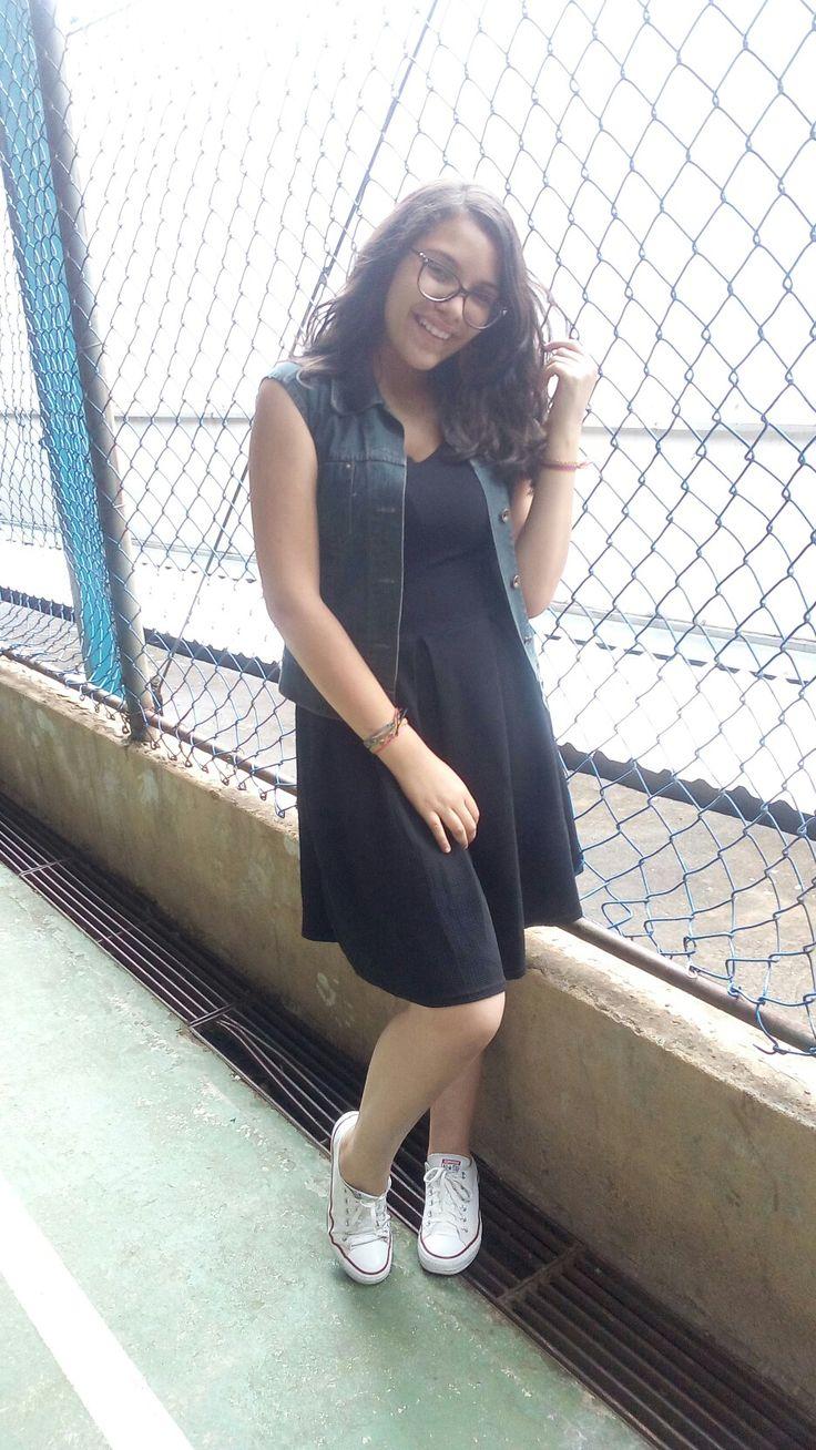 look despojado com um vestido preto básico, colete jeans por cima e um clássico all star branco