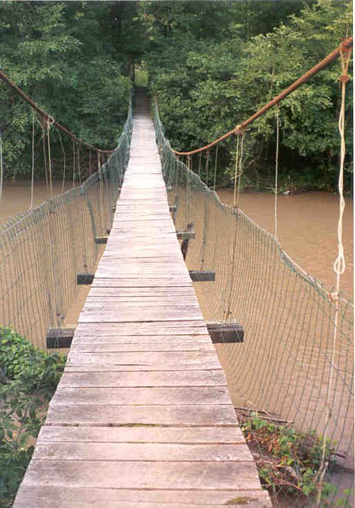 swinging bridge crossing swollen, muddy creek