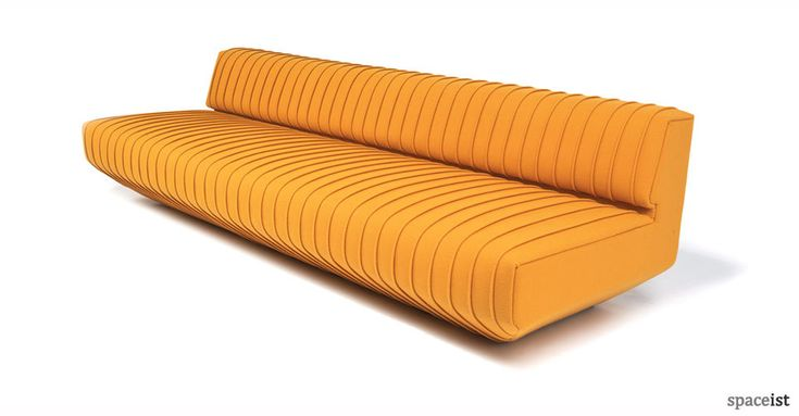 Unique sun yellow low reception couch with broad overlapping pleated upholstery.