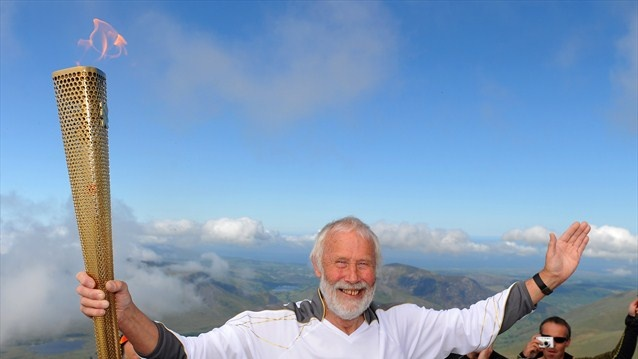 Mountaineer Sir Chris Bonington holds the Olympic Flame on the top of Snowdon during Day 11 of the London 2012 Olympic Torch Relay.