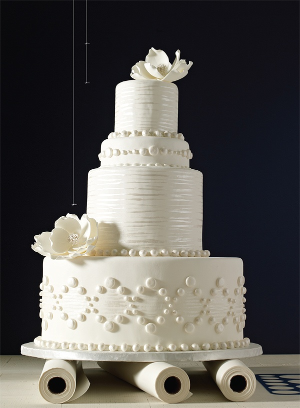 Love this monochromatic white wedding cake with white flowers and white pearl decor.