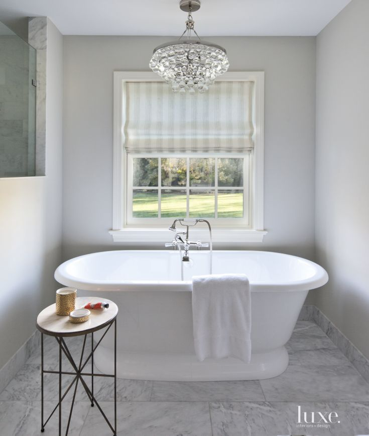 Victoria + Albert's elegant freestanding York tub was purchased at Ferguson Enterprises for the spa-like master bathroom. The roman shade is made of a Cowtan & Tout fabric. A Robert Abbey chandelier adds a glam factor.