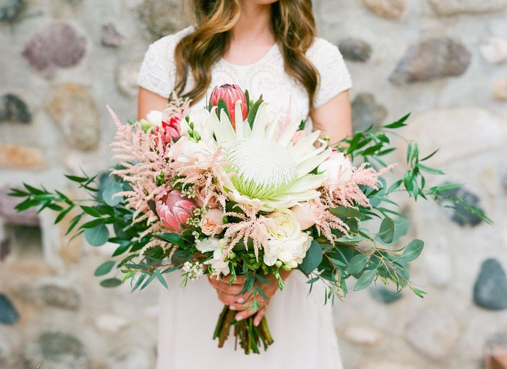 A tropical-inspired bouquet crowned with a white king protea, David Austin roses, pink astilbes, pink proteas, and Italian ruscus.