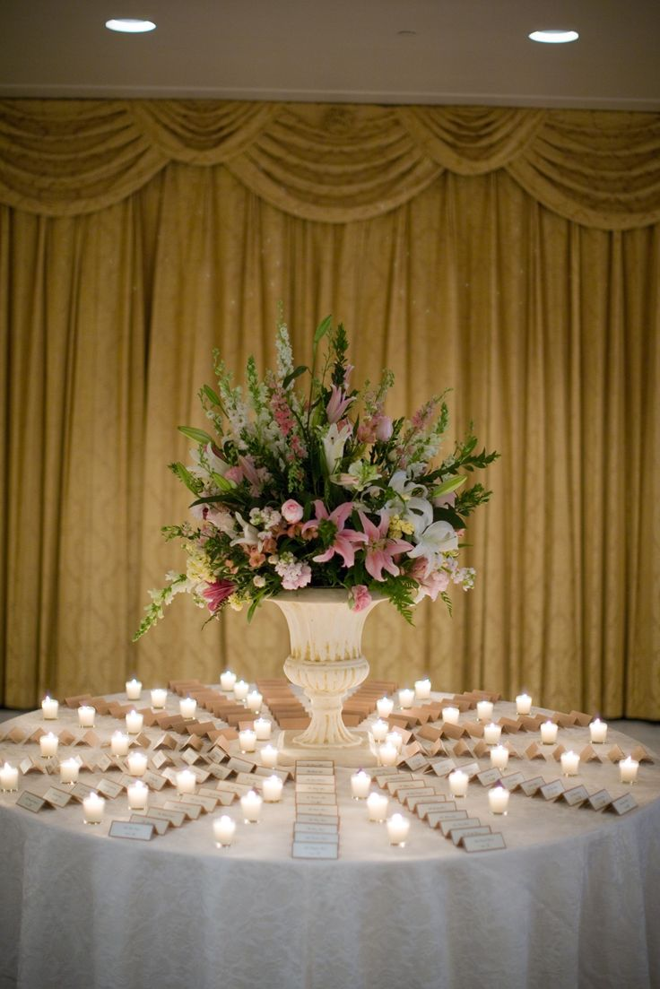 An impressive arrangement in a classic urn creates a romantic feeling for Kelly and Dayne's escort card table at Hotel Dupont. MK Photography.