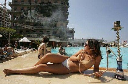 Visitors enjoy the swimming pool of Beirut's bombed landmark Saint-Georges hotel.