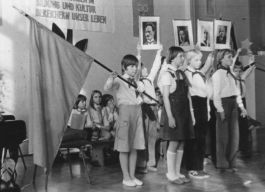 East German pioneers participating in a school ceremony during the 1980s. Notice the red flag. Surprisingly, it does not look red.