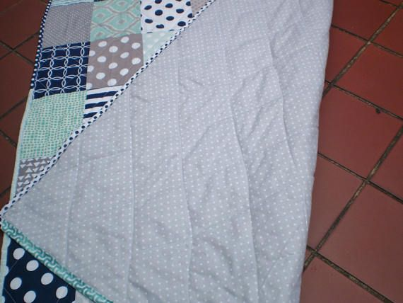 This terrific nautical themed patchwork quilt measuring 36 by 48 in navy blue, grey and mint green with chevrons, polka dots, stripes and quatrefoil would be perfect for the nursery for a boy or a girl; newborn, infant or toddler. (FYI: crib mattress is 27 BY 52)  As a traditional 3 layered quilt:  The quilt top, made of 100% quality designer cotton fabrics including Riley Blake, is machine pieced.  The middle layer of cotton batting adds warmth to the quilt.  The backing is made of an…