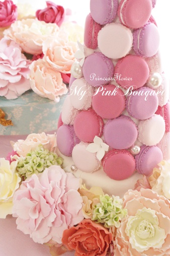 Gradient color macaron tower, pink, yellow, orange, mint, blue and chocolate colors.  Please put some flowers like the images shown in our macaron tower. And if possible, a white ribbon on top.
